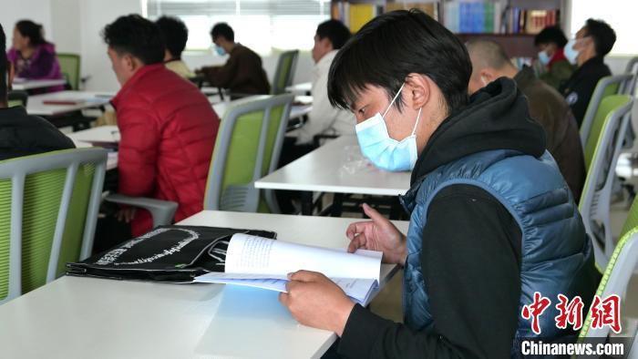 """图为正在阅读""""杰松达孜""""藏历法教材的学员。 谢牧 摄"""