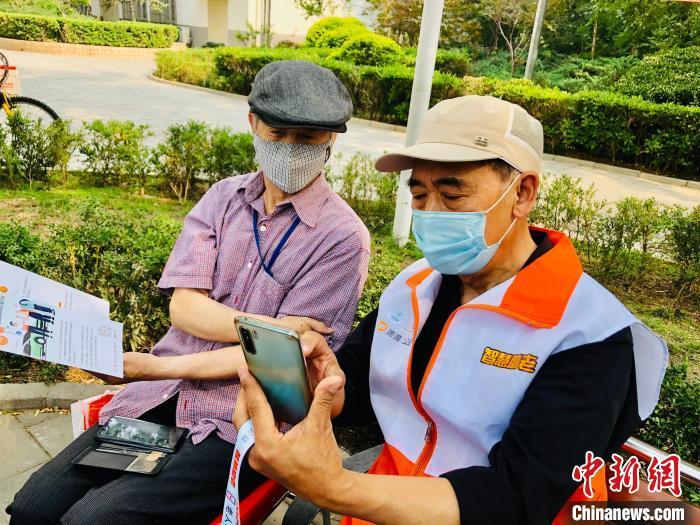 一位低龄老人志愿者(右)帮助另一位老人安装智能软件,并教其使用。 王祖敏 摄