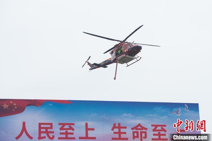 图为森林灭火演练现场,直升机前往火场上空开展侦查作业。